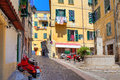 Small plaza among colorful houses in ventimiglia italy typical view of cobblestone street with scooters old residential buildings Royalty Free Stock Images