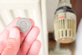 Small polish heating costs hand holding a one zloty coin infront of an out of focus thermostat for concepts like cheap savings Royalty Free Stock Photography