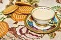 Small porcelain cup with white coffee and biscuits on embroided tablecloth old time flowered embroidered lace Stock Image