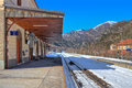 Small railway station in alps rails covered with snow along empty platform on the mountains Royalty Free Stock Photos