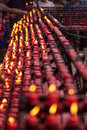 Small red candles lit by worshippers Royalty Free Stock Photo