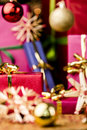 Small red gift box under baubles christmas gifts in vibrant colors between stars and focus is on the front plane of the crimson Royalty Free Stock Photos
