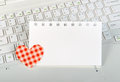 Small red hearts and sticky note on laptop keyboard Stock Image