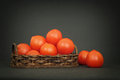 Small red tomatoes in a basket on dark table Royalty Free Stock Image