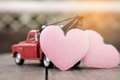 Small red toy car and pink hearts for valentine`s Day