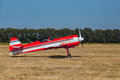 Small red and white private plane with propeller stands at the airport Royalty Free Stock Photo