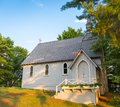 A small rural church in the woods, steeped in sunlight and shadow. Royalty Free Stock Photo