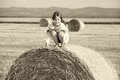 Small rural girl on the straw after harvest field with straw bal Royalty Free Stock Photo