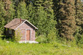 Small rural log cabin hut on clearing in forest old solid shelter standing at the edge of a lush green perfect as a peaceful Stock Image