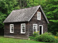 Small rustic wood house in trees Royalty Free Stock Photo