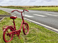 Small rusty bicycle painted in red on a roadside in a rural area Stock Image