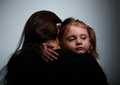 Small sad daughter hugging her mother with love on dark Royalty Free Stock Photo