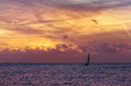 Small sailboat and sunset with red clouds and blue water Royalty Free Stock Photo