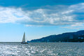 Small sailing boat in blue and calm sea yacht water ocean shore the background Stock Photo