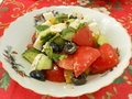 A small salad on a plate tomatoes cucumbers olives cheese fresh paprika Stock Photo