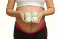 Small shoes for the unborn baby in the belly of pregnant woman isolate Royalty Free Stock Photos