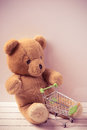 Small shopping cart and a teddy bear conceptual image for sale of toys or children s fantasies little Stock Image