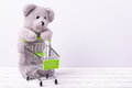 Small shopping cart and a teddy bear conceptual image for sale of toys or children s fantasies little Royalty Free Stock Photo