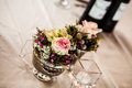 Small silvers an image of a silver flower vases filled with vibrant wild flowers and delicate roses Stock Photo