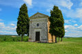 Small single chappel in tuscany photo shows away from any building the is surrounded by cyprysses midday sun makes grass Royalty Free Stock Photo