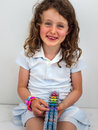 Small smiling girl with a band loom in summer dress Stock Photo