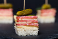 Small snacks canape with salami cheese and pickle on skewer on a black slate plate shallow depth of field Royalty Free Stock Photography