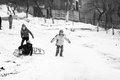 Small southern romanian village scenes from a moody winter with children playing with sledges and enjoying the snow Royalty Free Stock Photos
