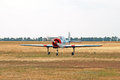 A small sport aircraft rolls on the field Stock Images