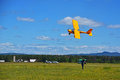 A small sports plane flies at a low altitude. Man takes flight on video.