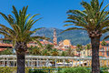 Small square palms and colorful houses in menton on town with bell tower on background france Royalty Free Stock Photos