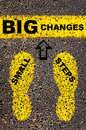 Small steps big changes message conceptual image with yellow paint footsteps on the road in front of horizontal line over asphalt Stock Photos