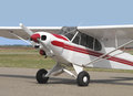 Small tail-wheel red and white airplane. Royalty Free Stock Photo