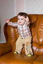 The small toddler on a leather brown sofa stretc Stock Photos
