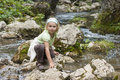 Small tourist sitting by a mountain river