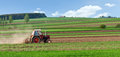 Small tractor harrow on the spring field Royalty Free Stock Images