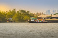 Small tugboat is pulling a large shipping barge up the Chao Phra Royalty Free Stock Photo