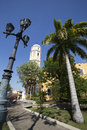 Small urban park and the yellow evangelistic cathedral with a clear blue sky an old city lighting ciudad bolivar Royalty Free Stock Image