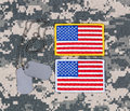 Small USA flag patches and ID tags on military battle dress unif Royalty Free Stock Photo