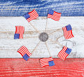 Small USA flags in circle formation around Liberty coin on rusti Royalty Free Stock Photo