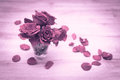 Small vase with red roses and petals on wooden table in soft focus image retro effect Royalty Free Stock Image