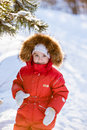 Small very cute girl in a red suit with fur hood costs about tre