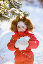 Small very cute girl in a red suit with fur hood keeps the snow