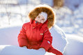 Small very cute girl in a red suit with fur hood sits in the sno