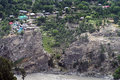 Small village reside close to falling rock formation along river at himachal pradesh cascade of houses bank Stock Photo