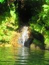 A small waterfall falls into a small lake Royalty Free Stock Photo