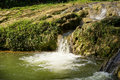 Small waterfall by the lake landscape with on a summer day and green moss on stones Royalty Free Stock Image