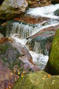 Small waterfall by large rocks Stock Photos