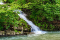 Small waterfall on a little mountain stream coming out of the forest falls to Royalty Free Stock Image