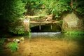 Small weir on river flows out from cave cold water of small river flow over small stony weir stony and rusty construction of we Stock Photos