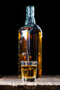 Small whiskey shot on an old wooden table Royalty Free Stock Photo